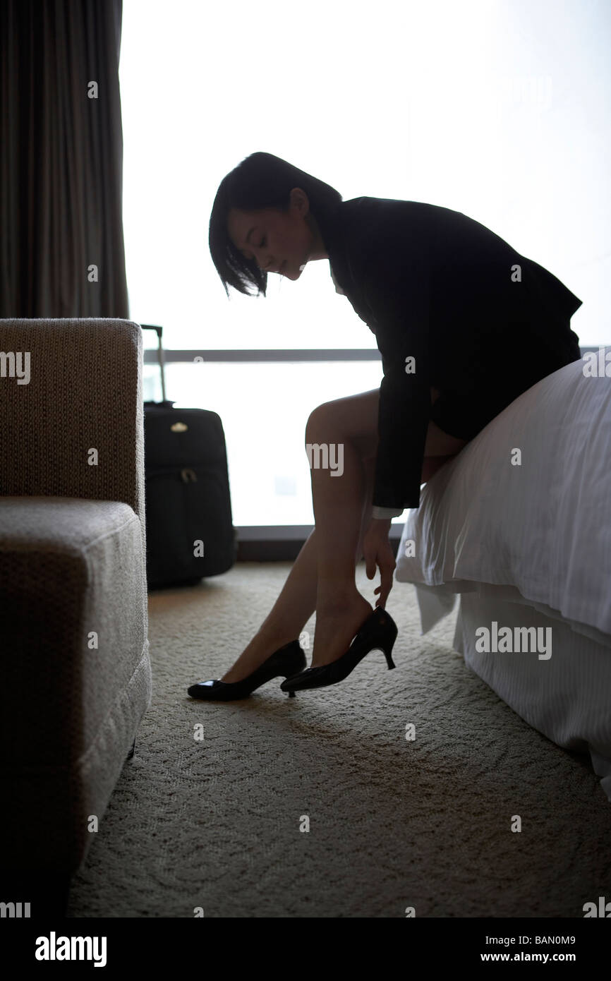 Woman in business attire putting on her shoes - Stock Image