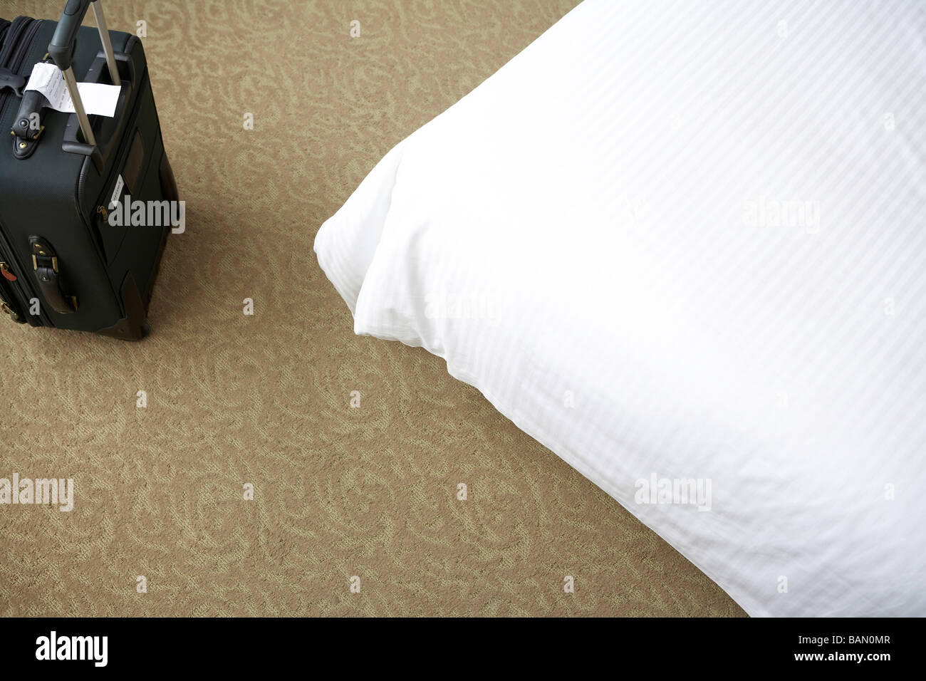 Suitcase in front of a bed - Stock Image