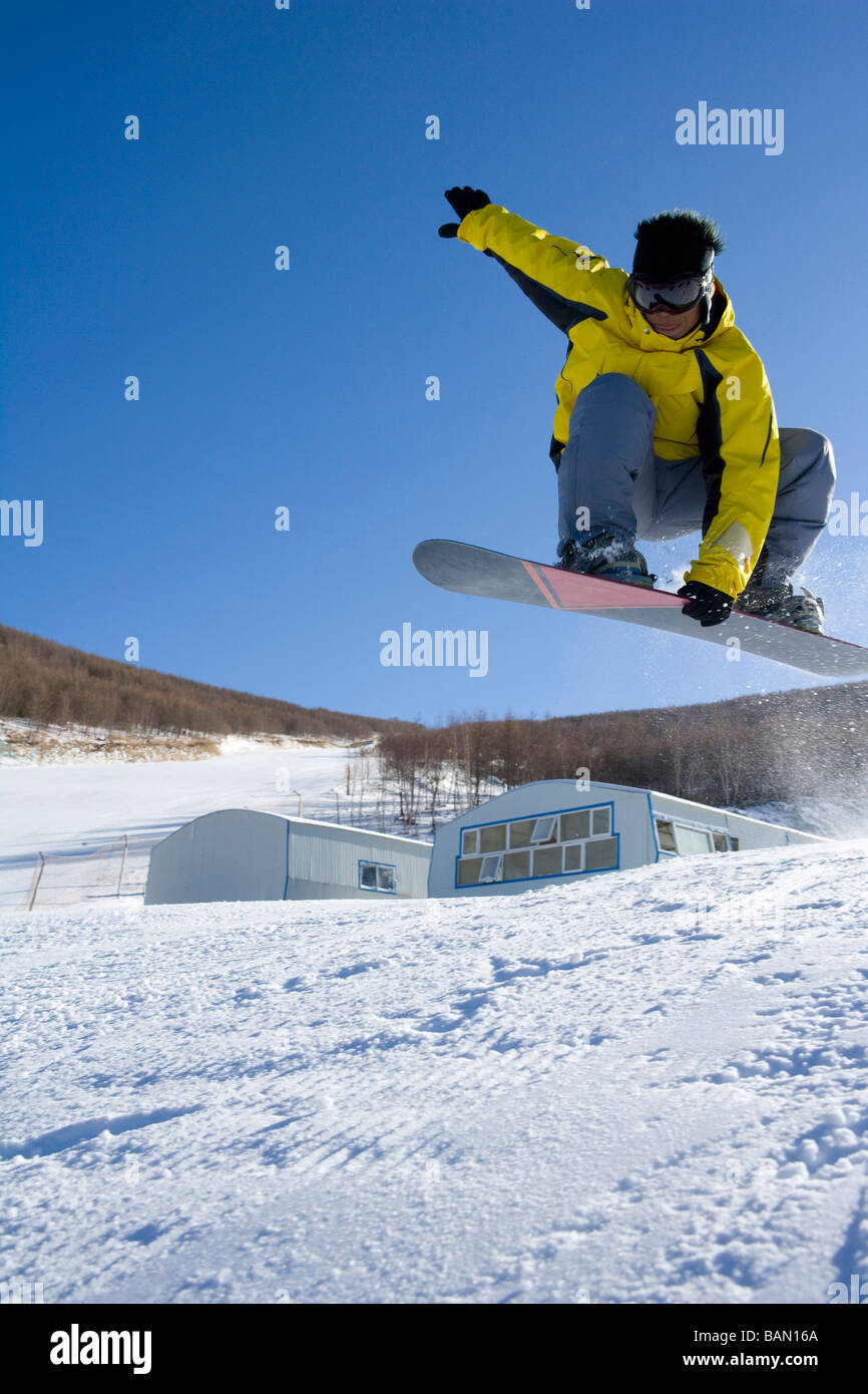 Young man on his snowboard mid-air Stock Photo