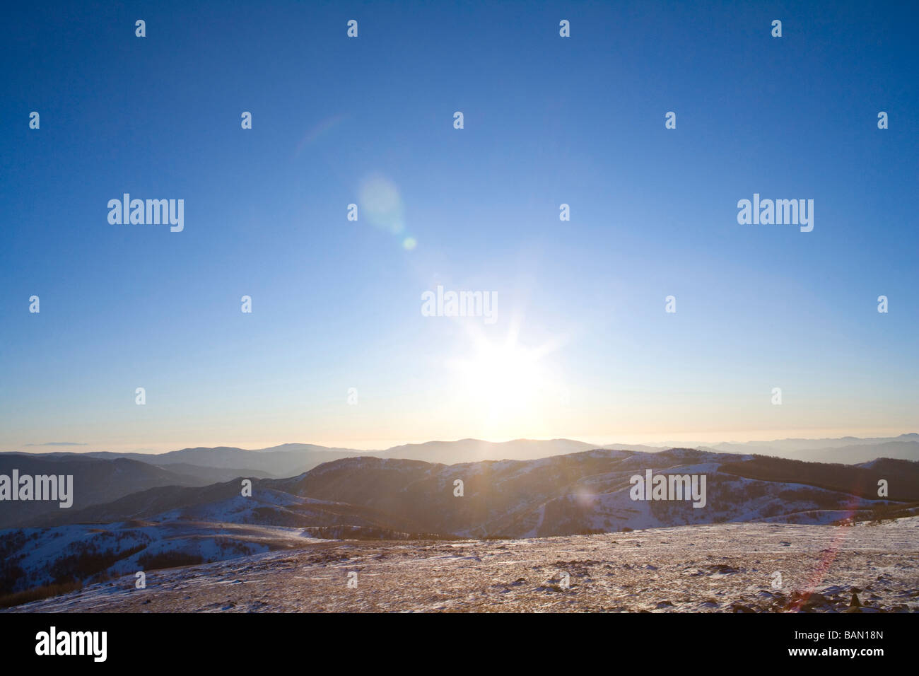 View of the sun setting over a mountain landscape - Stock Image