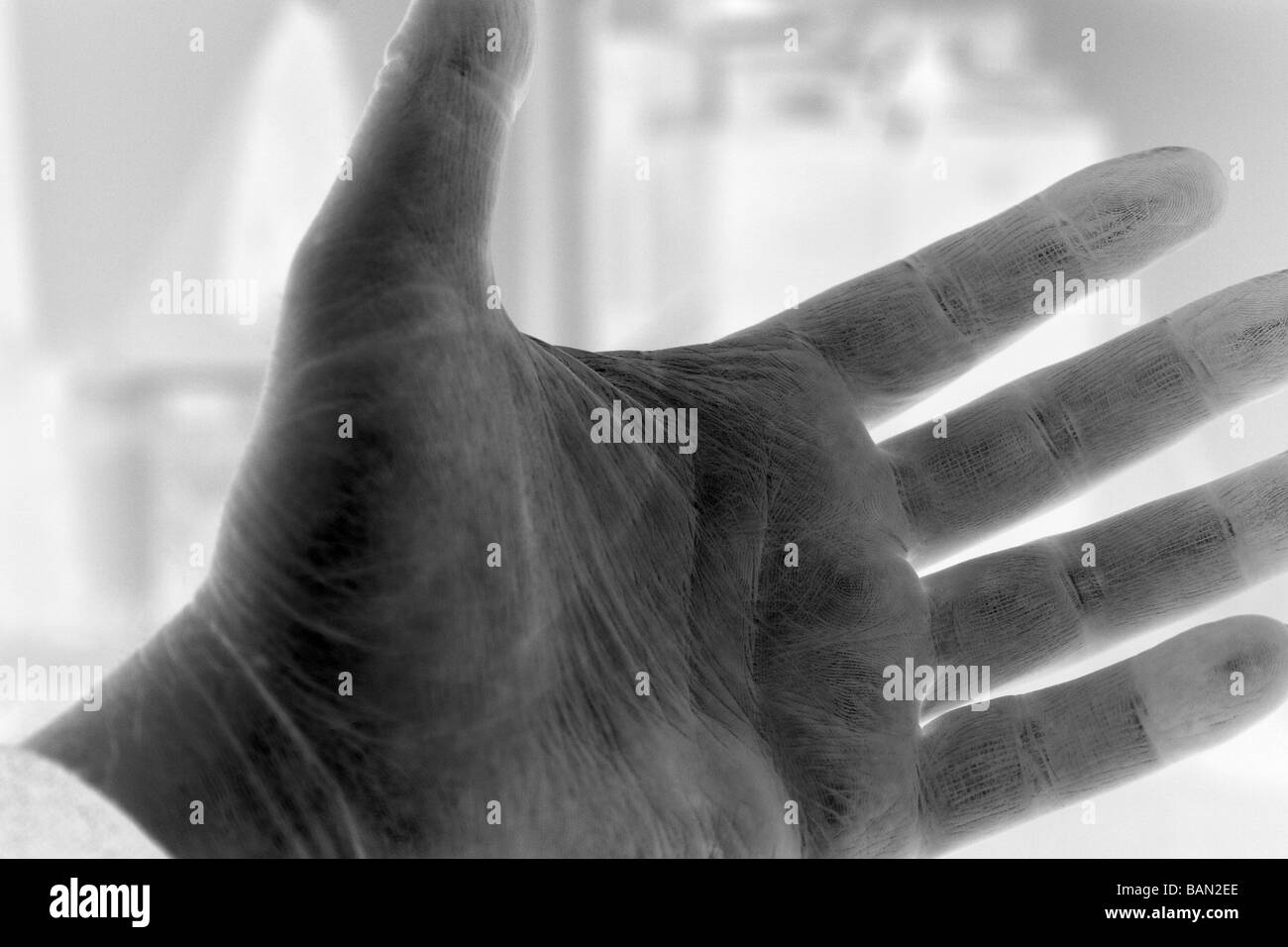 Horizontal black white photograph (digitally altered to show as negative) of man's outstreted hand palm side - Stock Image