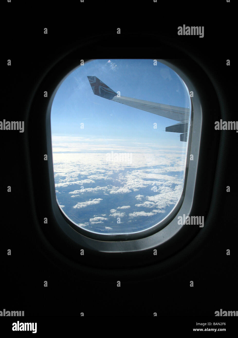 wing and sky at high altitude through the window of a passenger jet airliner - Stock Image