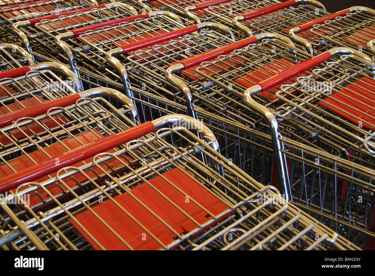 horizontal color photograph of  red trimmed grocery carts - Stock Image
