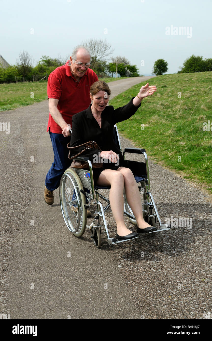 Elderly carer pushing woman in a wheelchair in the English countryside UK - Stock Image