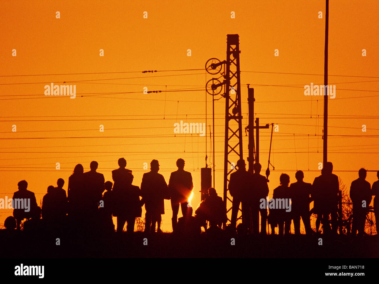 spectators listening to openair event at sunset - Stock Image