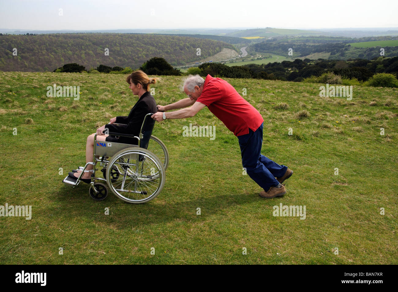 Carer pushing woman in a wheelchair in the English countryside UK - Stock Image