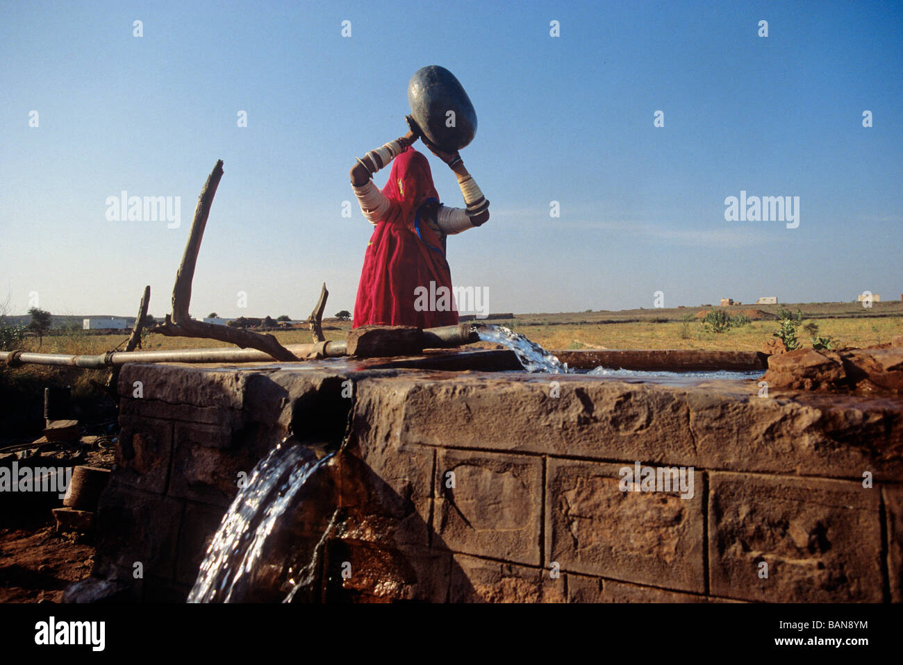 woman carrying water mug from water well state of rajasthan india - Stock Image