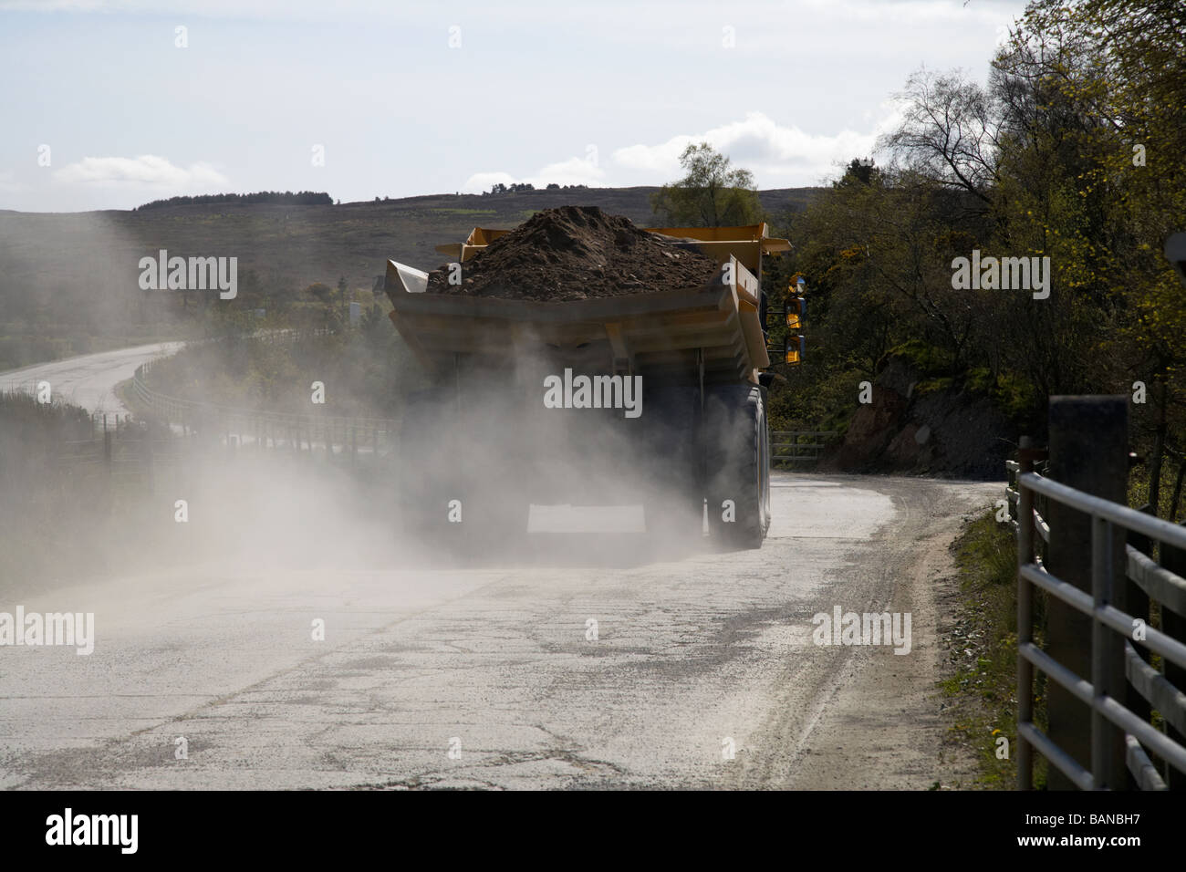 large dumper truck throwing up dust carrying a load of sand and gravel from the quarry at lough fea county tyrone - Stock Image