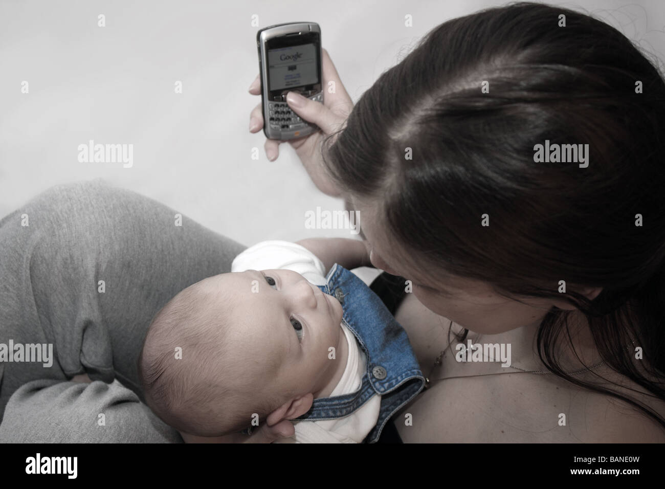 A young mother with her baby boy using a Blackberry PDA mobile phone searching the internet on Google search engine - Stock Image
