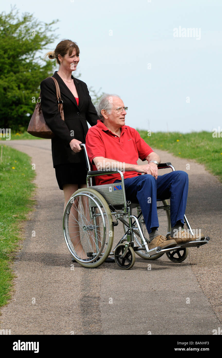 Female carer pushing elderly man in a wheelchair in the English countryside UK - Stock Image