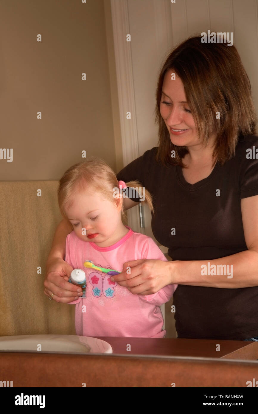 Woman and girl; Mother brushing daughter's teeth - Stock Image