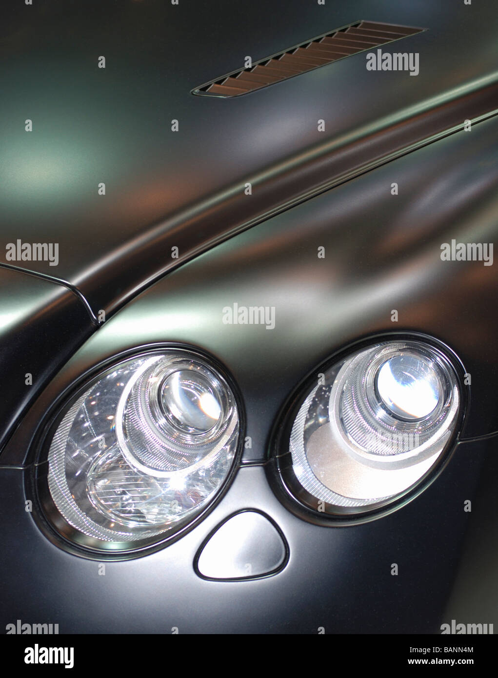 Close up of a stylish modern sports car front twin headlamps - Stock Image