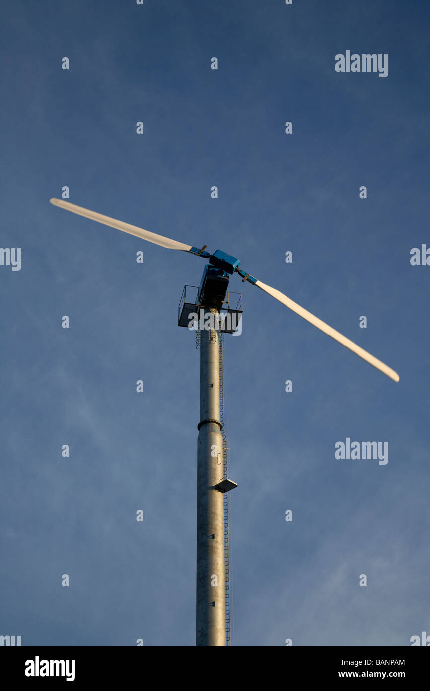 medium single wind turbine set in a natural environment to generate electricity for a small business premises - Stock Image