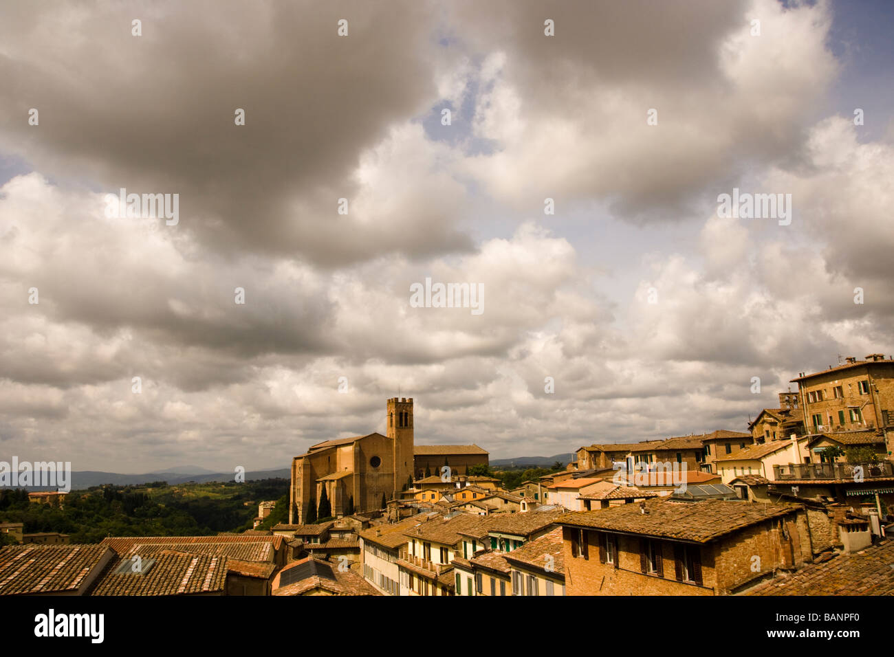 Wide-angle rooftop view of Ancient walled city of Siena Italy and San Domenico cathedral also known as Basilica Cateriniana Stock Photo