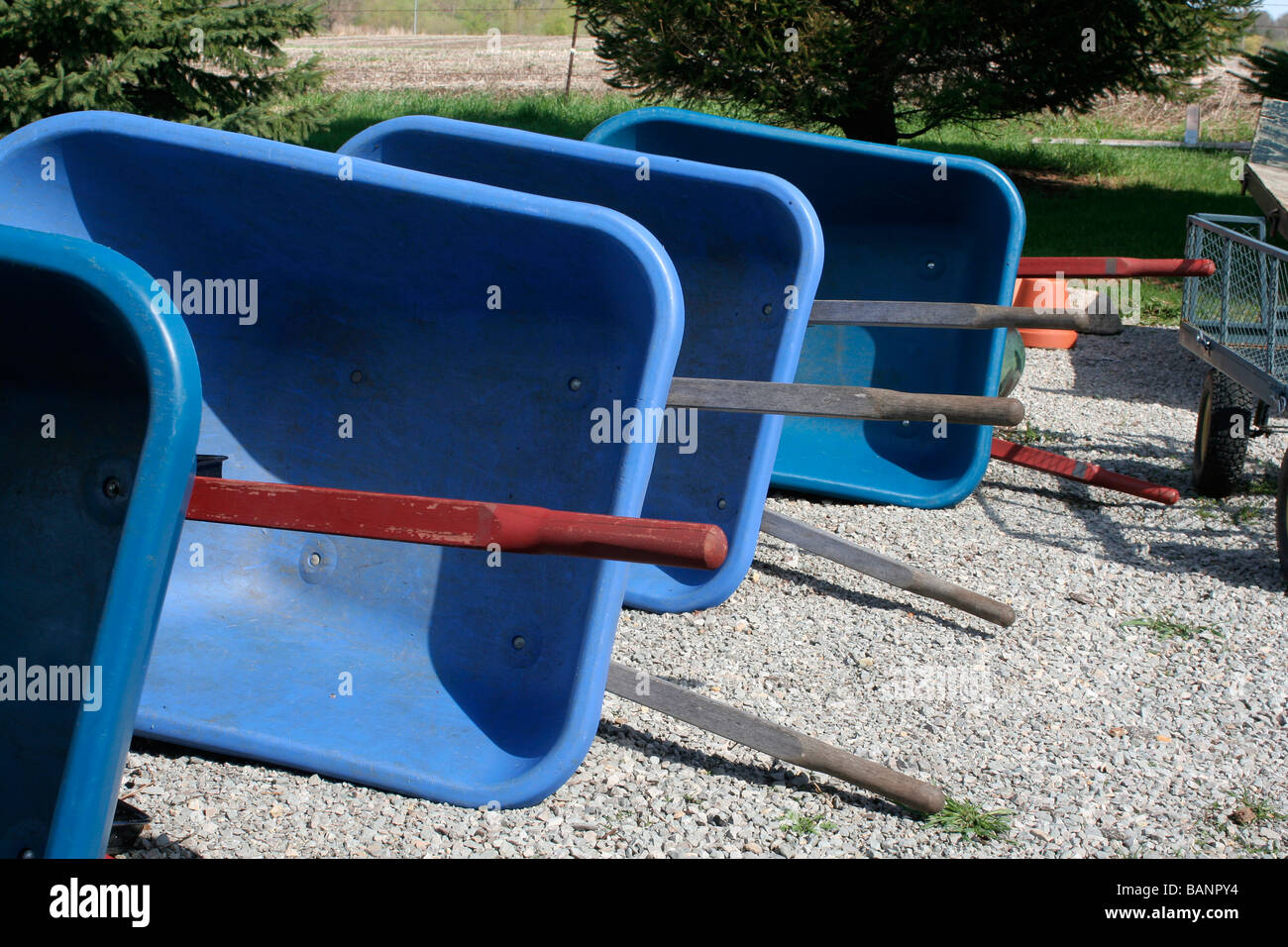 Wheelbarrows waiting to do spring work in nursery - Stock Image