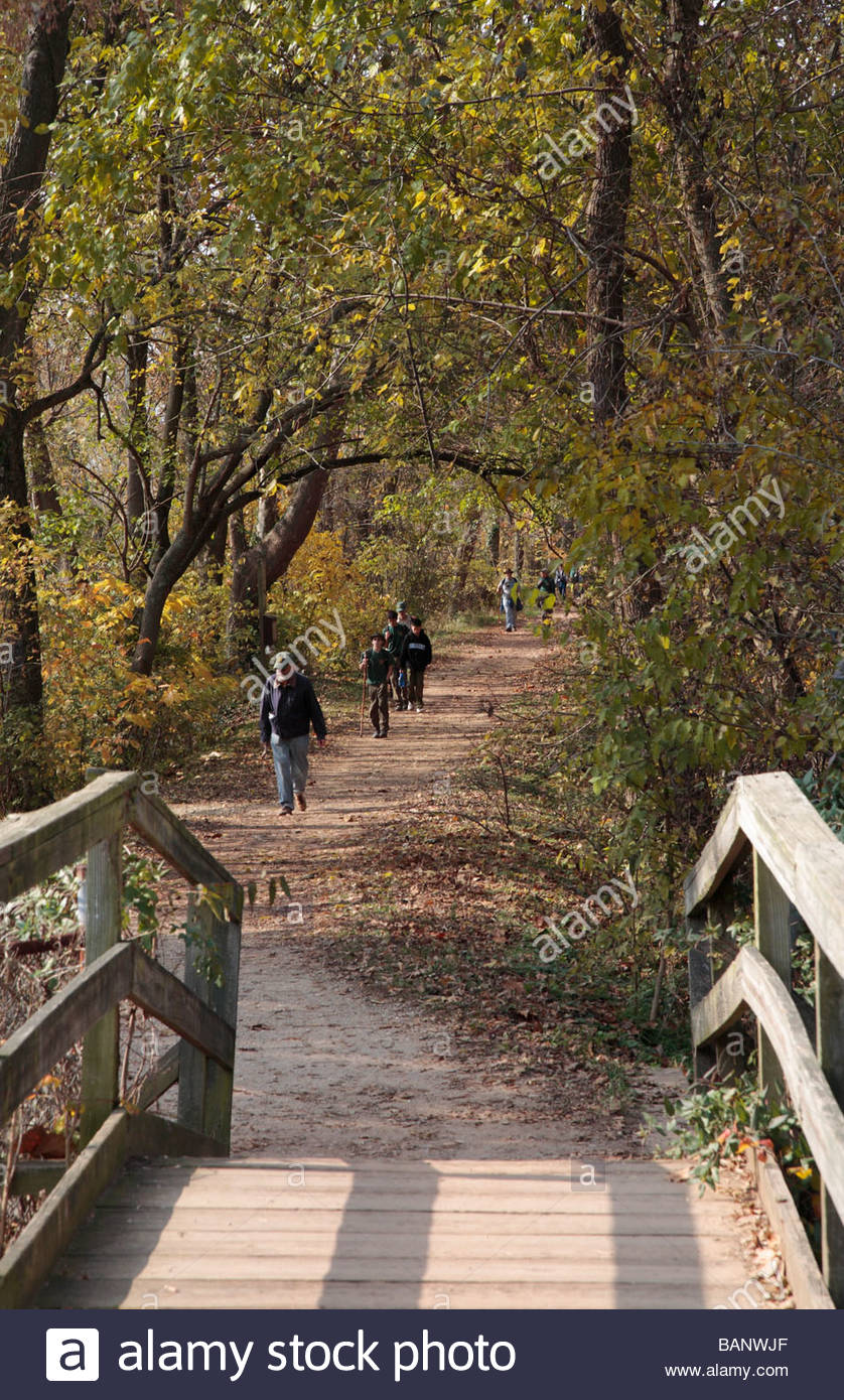 Hikers on the towpath approach the aqueduct at Rileys Lock on the C&O Canal. - Stock Image