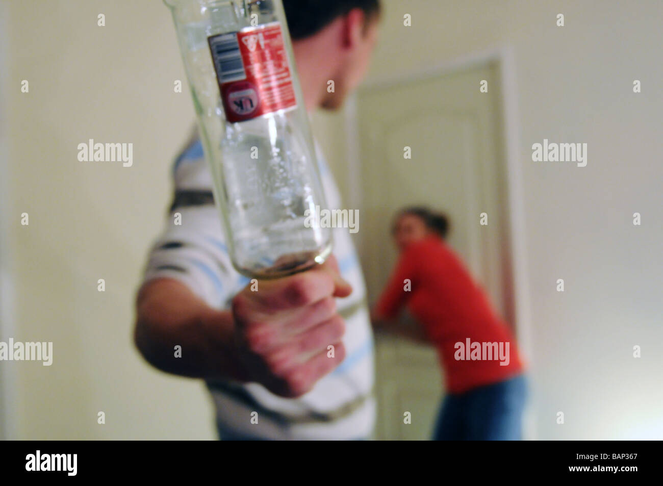 Young male physically abusing a young woman in their twenties with a glass bottle - Stock Image
