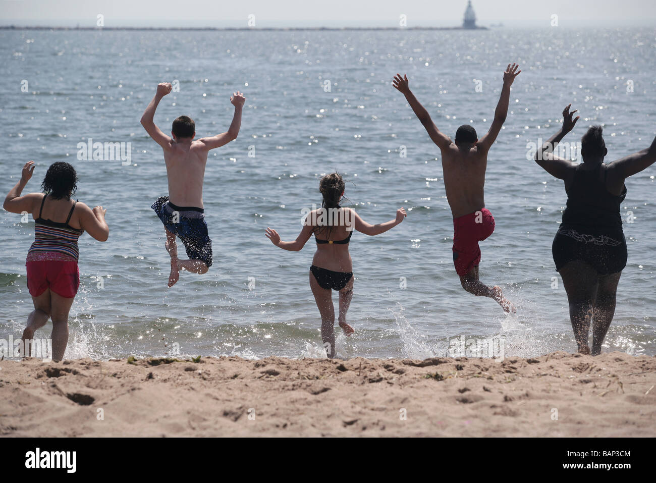 Five teenagers of different race and gender run and jump into the water on a hot summer day. - Stock Image