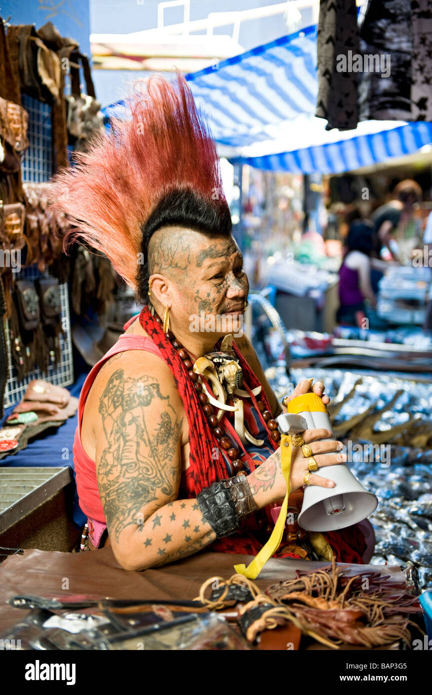 Tattooed Vendor with Mohawk in Chatuchak Weekend Market, Bangkok, Thailand. - Stock Image