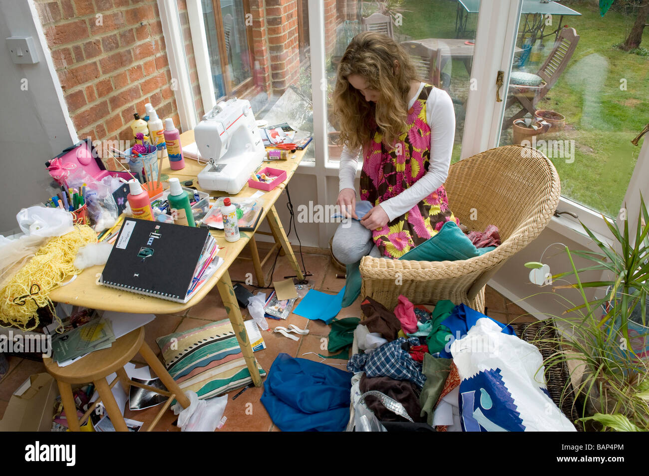 Working at home on gcse art course work a girl gets on with some sewing for textiles - Stock Image