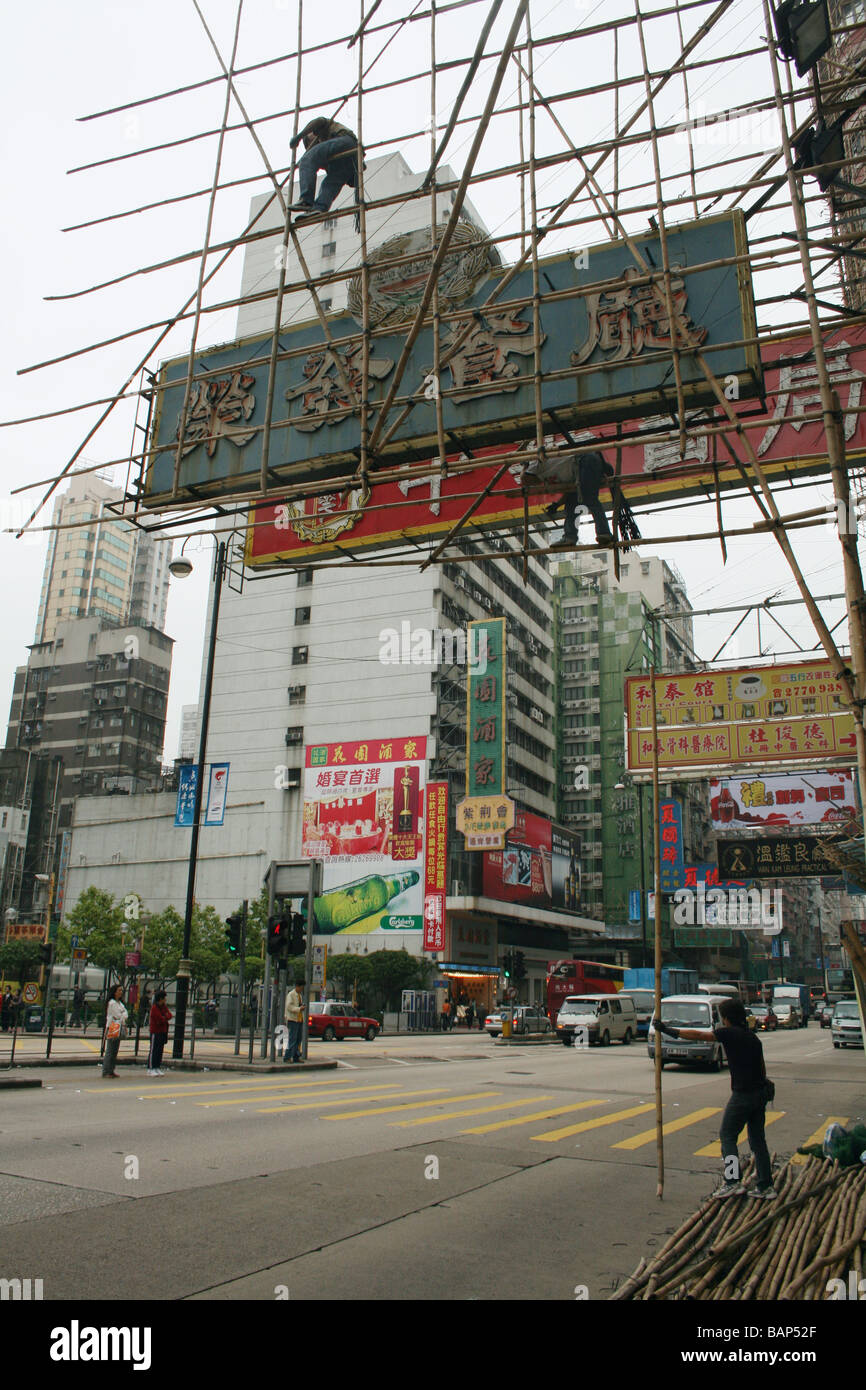 Workers constructing bamboo scaffolding around sign Hong Kong  April 2008 Stock Photo