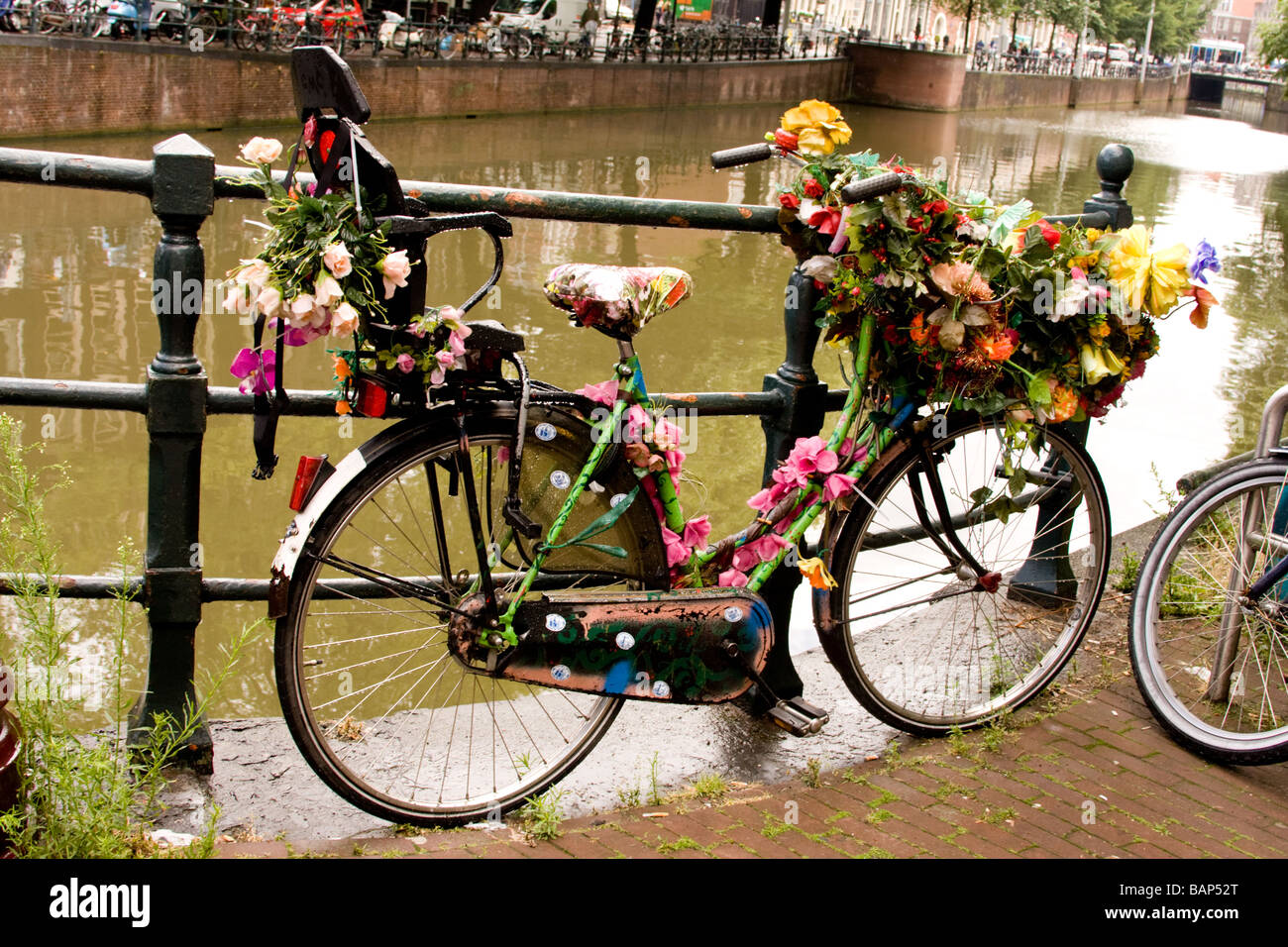 bicycle festooned or garlanded with articficial flowers on a canal bank in Amsterdam Holland - Stock Image