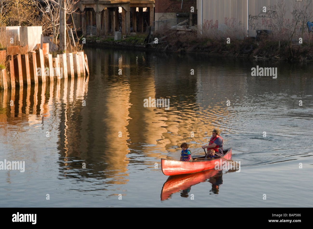 Man and two children canoe on the Gowanus Canal - Stock Image