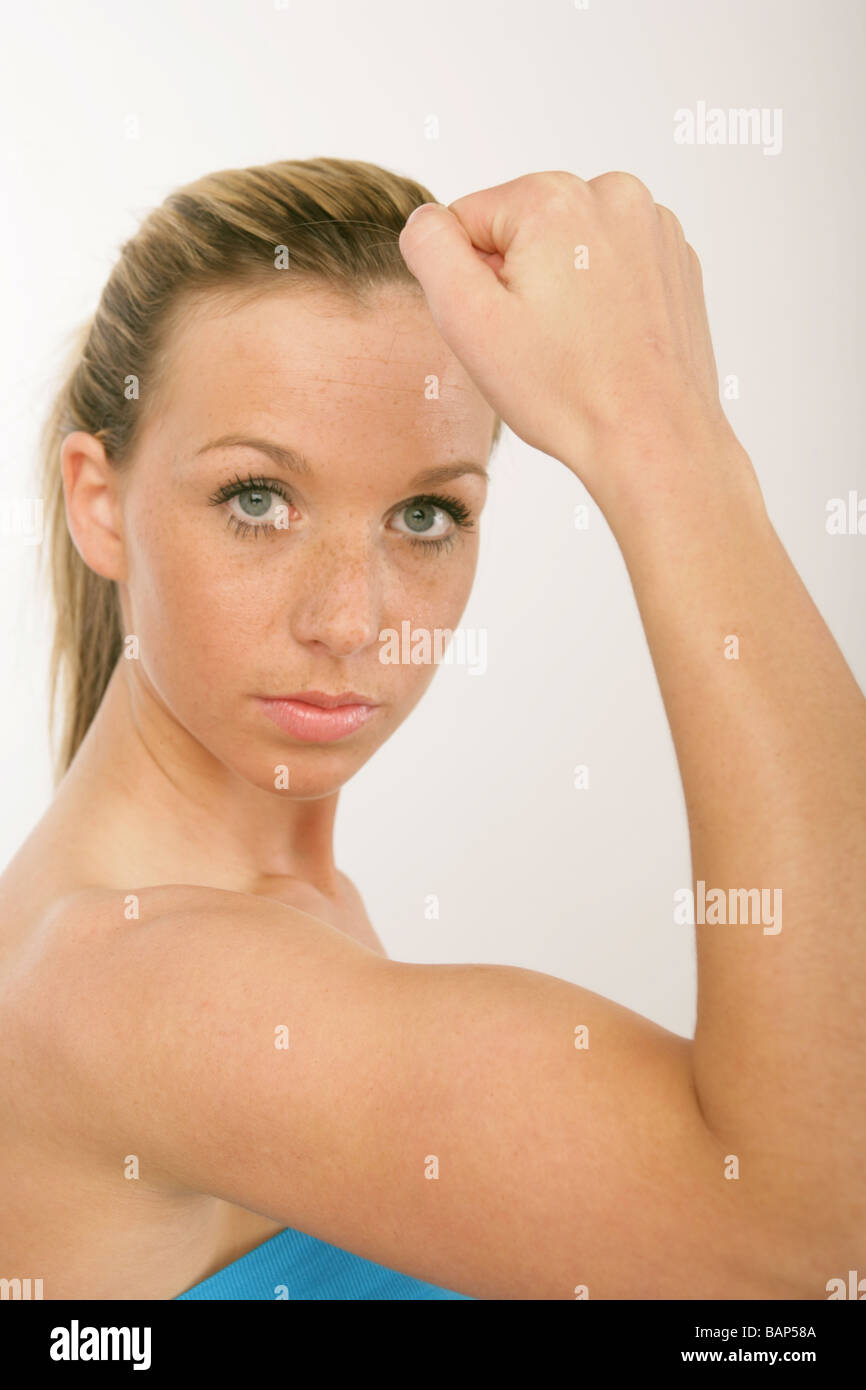 Well Toned Blonde Woman Flexing Her Bicep Muscles Stock Photo