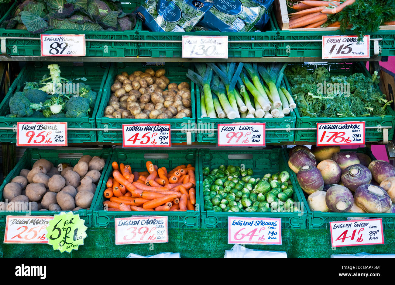 Mixed fresh vegetables in tiered display outside a greengrocer shop or store in England UK - Stock Image