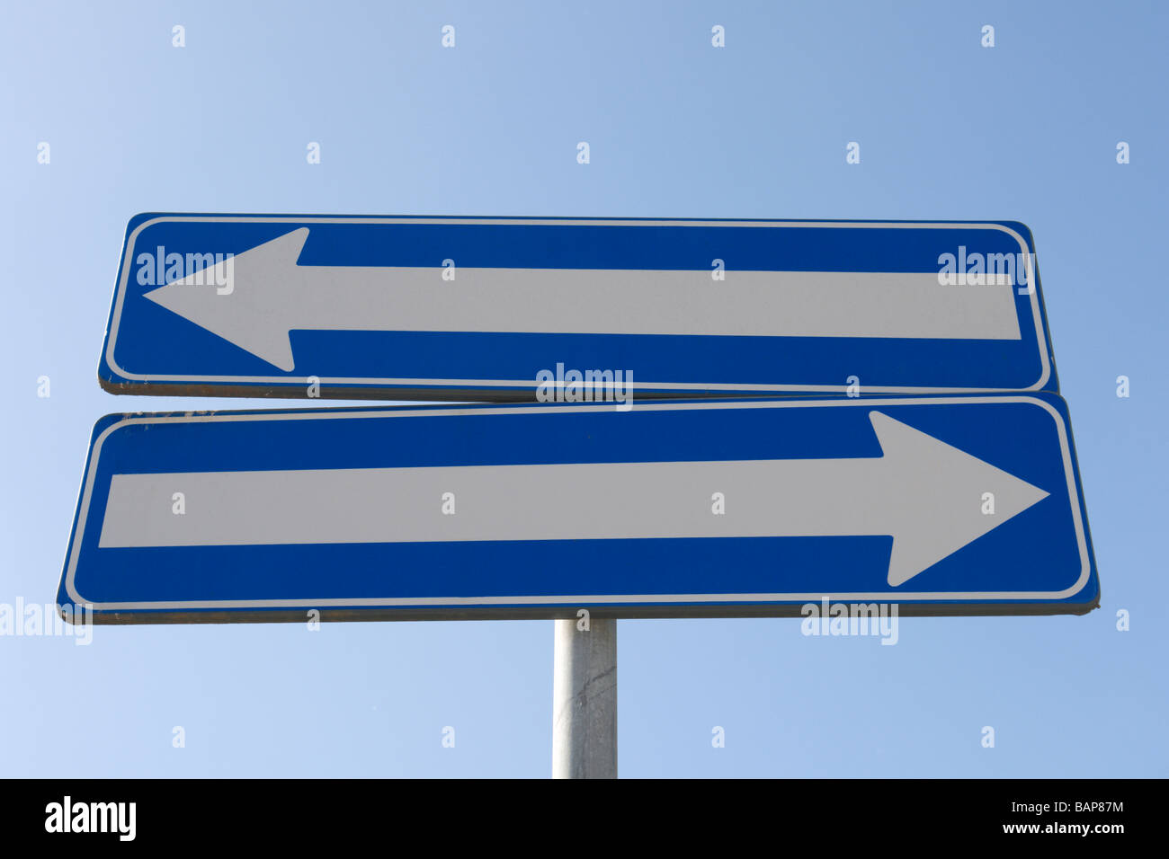 Road sign with two one way signs indicating opposite directions - Stock Image