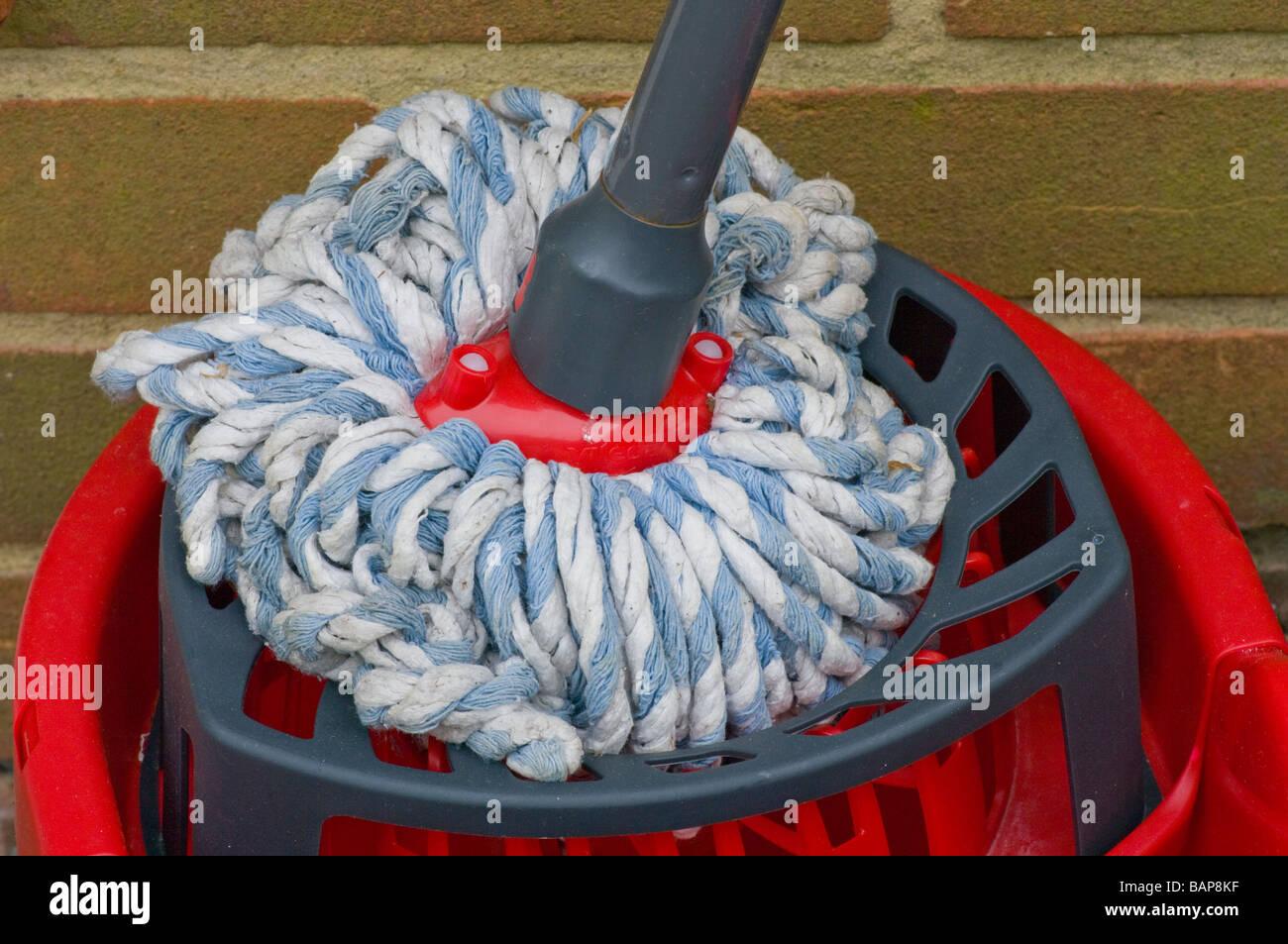 Floor Mop and Red Plastic Bucket - Stock Image