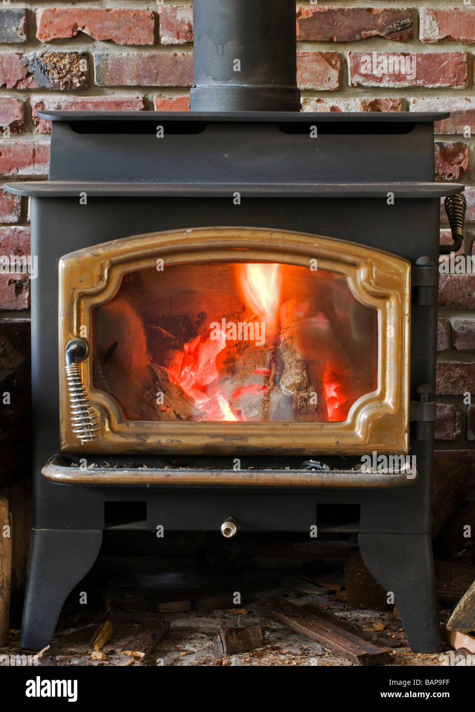 Cozy fire in wood burning stove glows brightly. - Stock Image