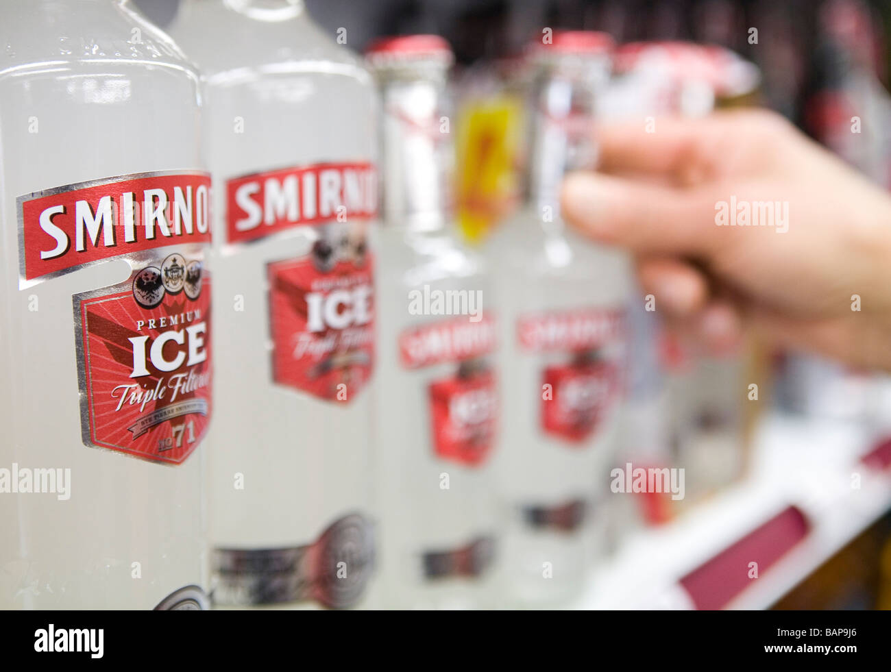 A customer takes a bottle of Smirnoff Ice from the shelf in an off license - Stock Image
