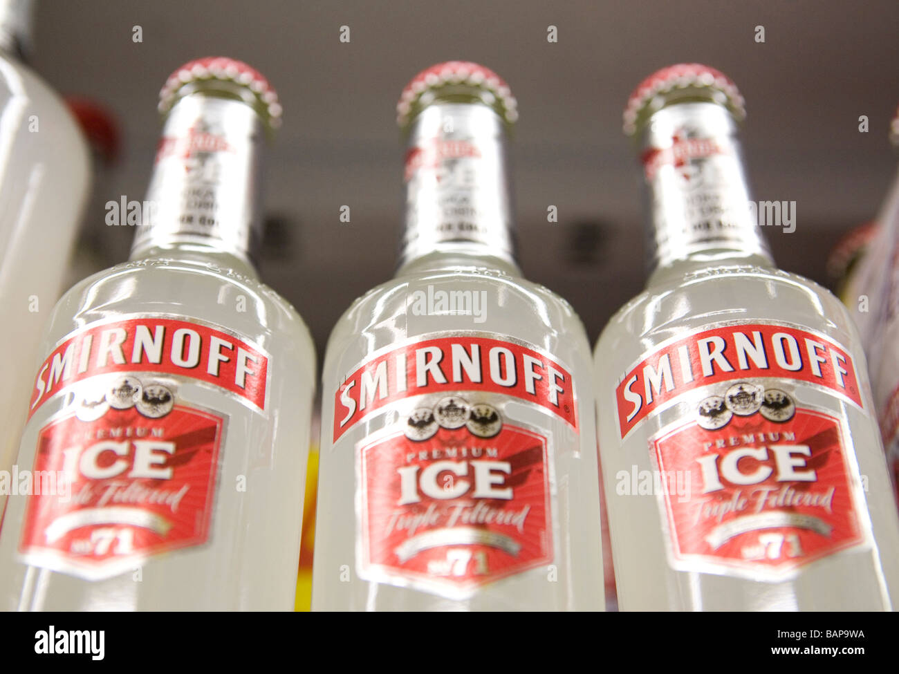 Bottles of Smirnoff Ice on the shelf in an off license - Stock Image