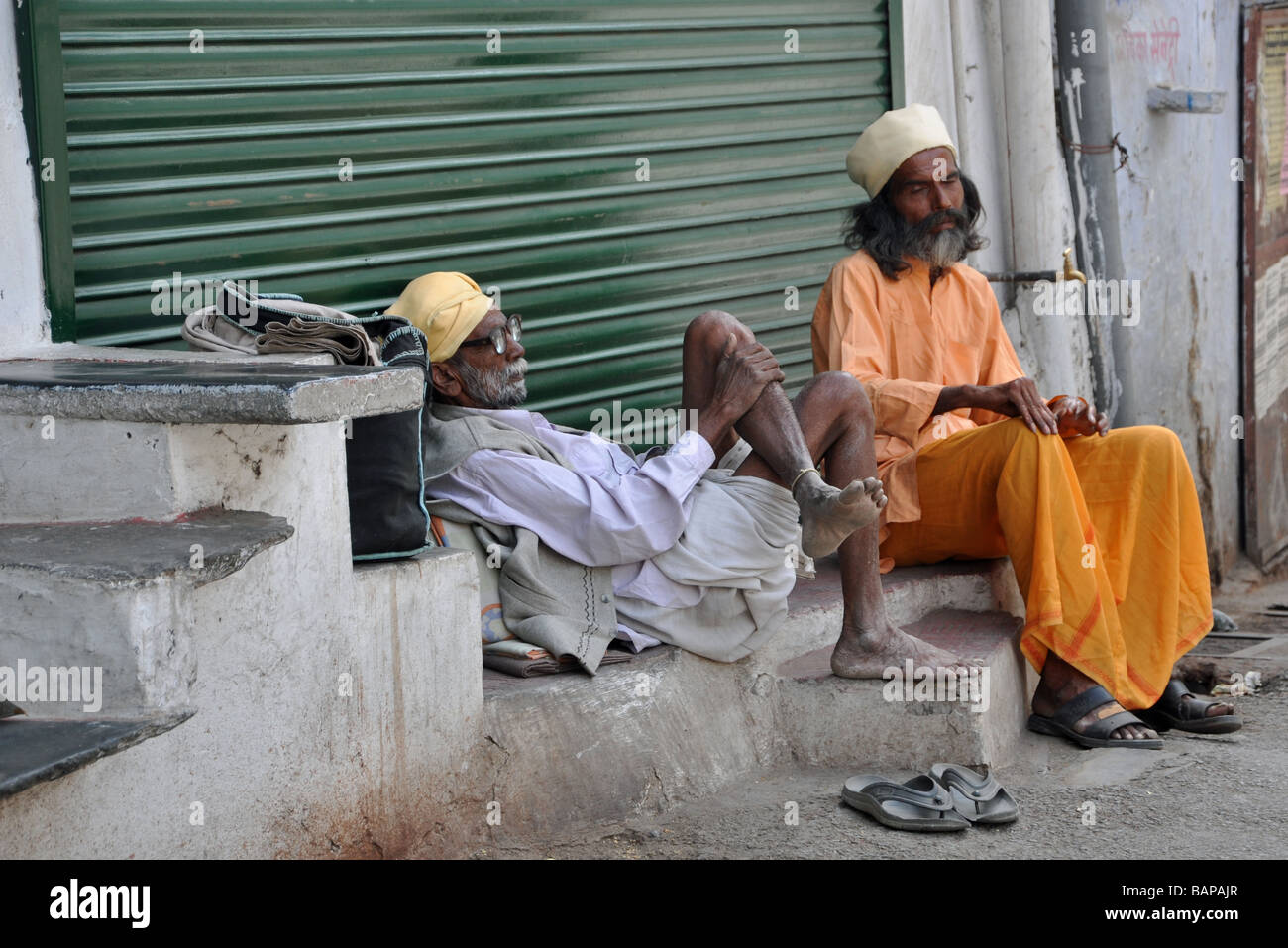 An old man sitting companionably with a Sadhu in Udaipur, India - Stock Image