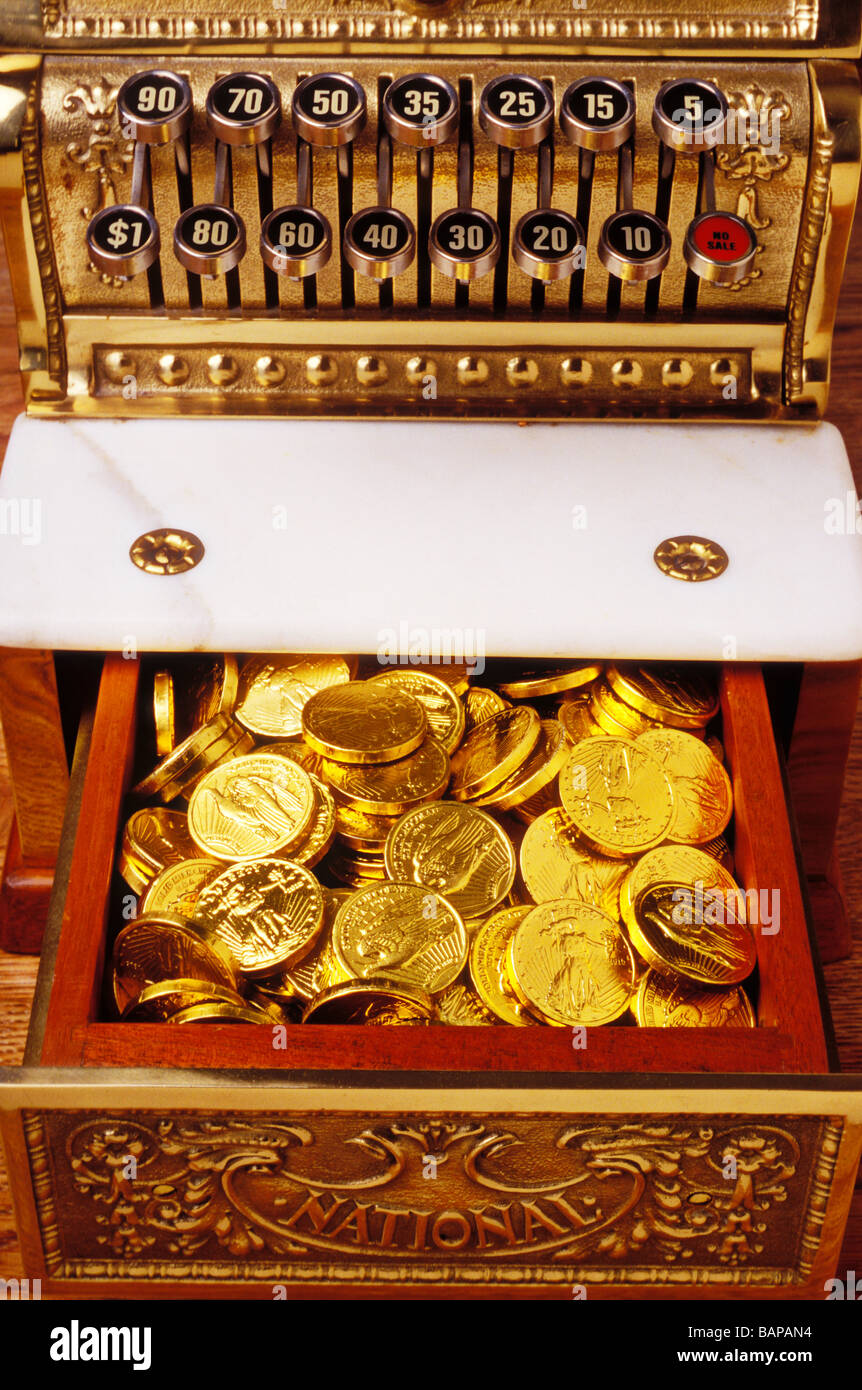 Old cash register with gold coins - Stock Image