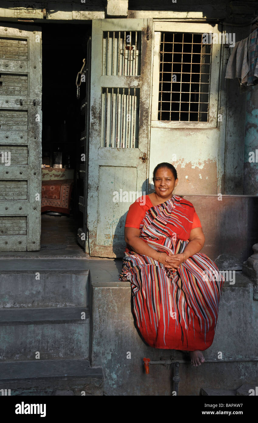 A Woman in a Red Sari relaxing in an Ahmedabad Street - Stock Image