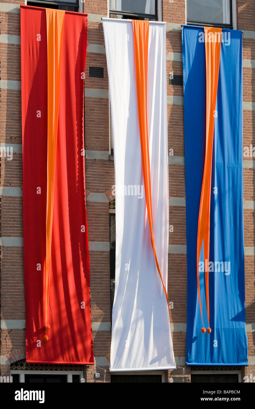 Dutch national flag, banners in the colors of the Dutch flag. On an Amsterdam canal on Queensday. - Stock Image
