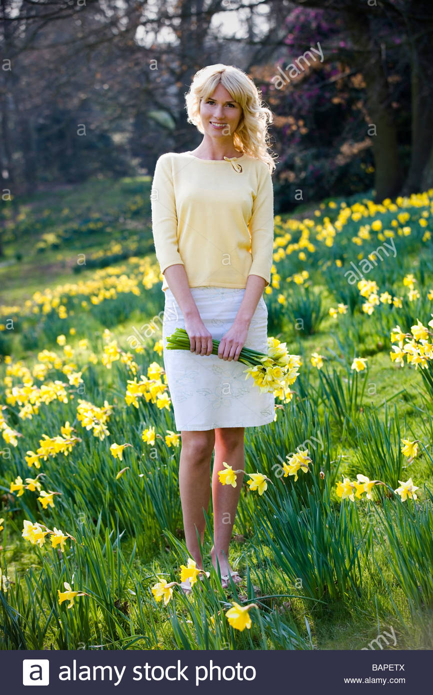 A young woman holding a bunch of daffodils - Stock Image
