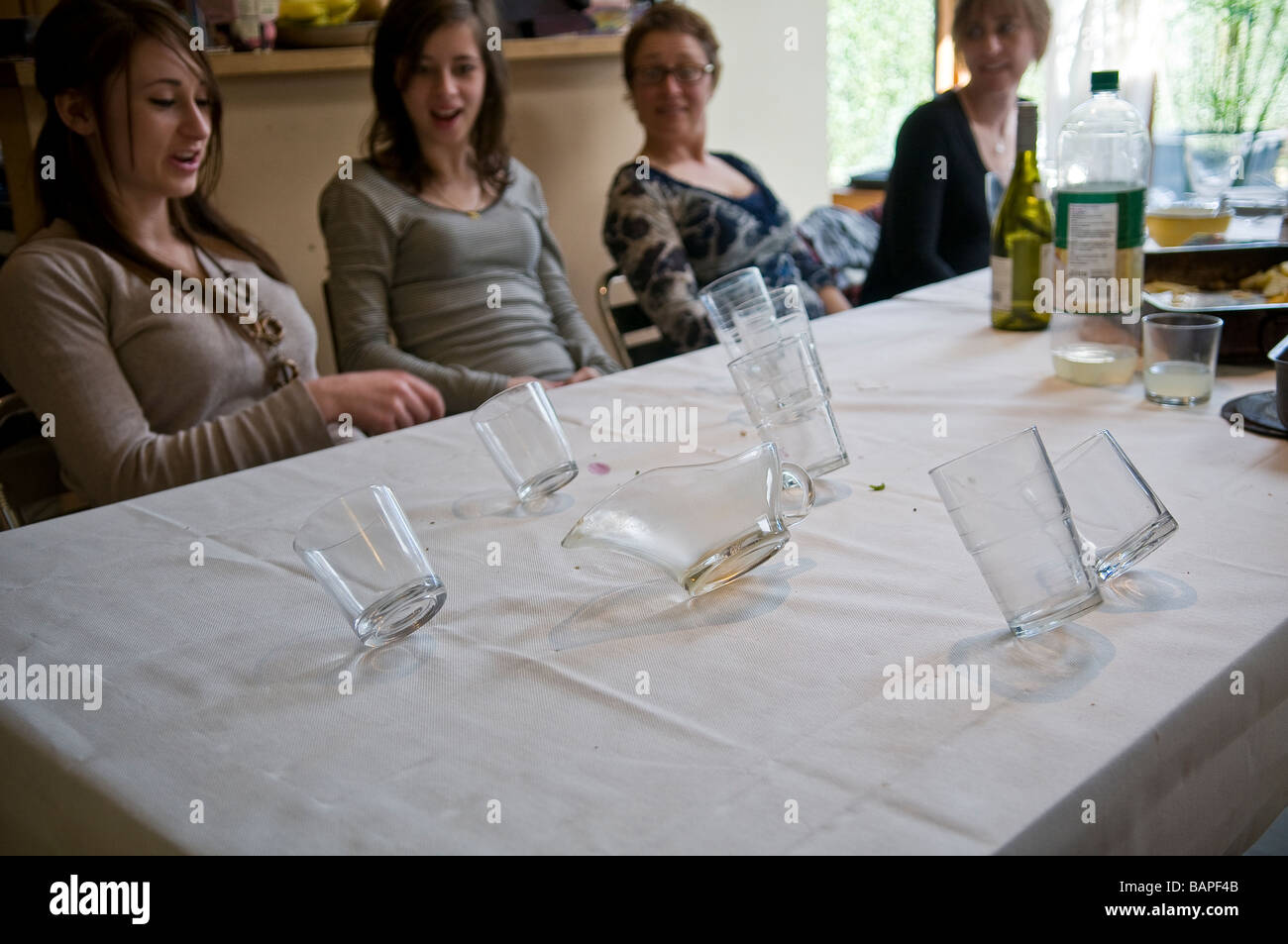 Poltergeist activity causes glasses to tip over during family meal - Stock Image