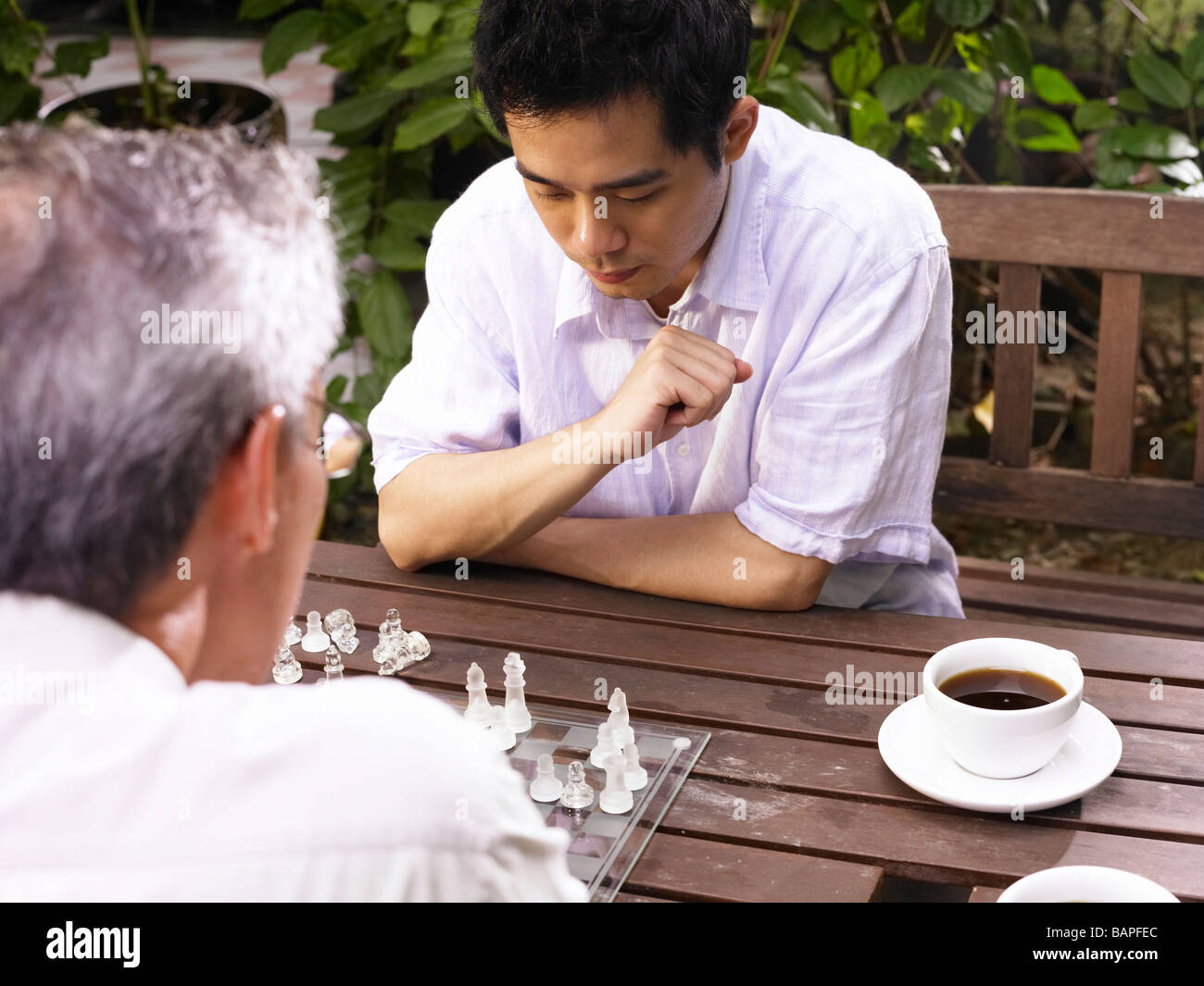 father and son playing chess game at garden - Stock Image