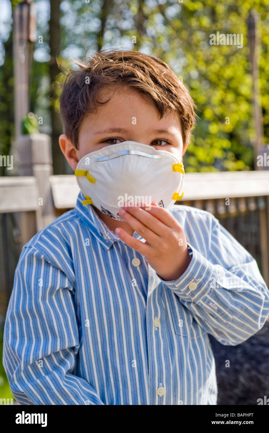 Three and 1/2 year old Hispanic boy wears a N95 rated respirator mask as protection against the Swine Flu - Stock Image