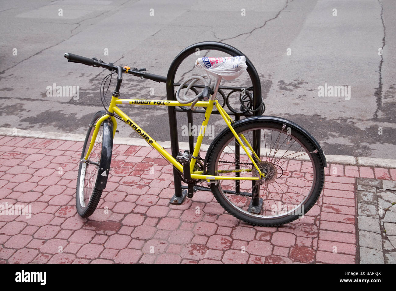 A bicycle locked to a bike rack with a bicycle lock The seat is covered with a plastic bag to protect it from the - Stock Image
