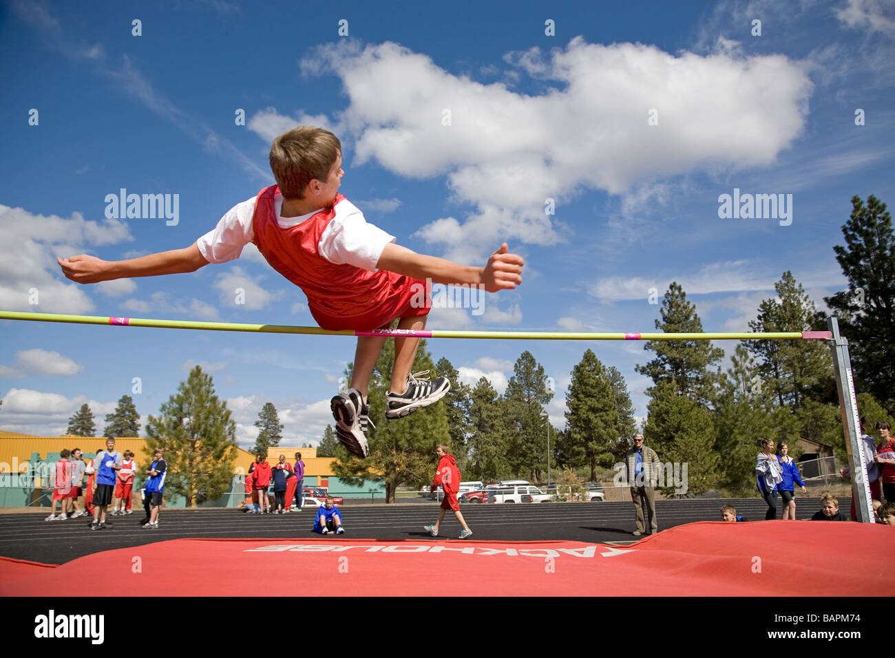 Boy's middle school and high school track meet with boys doing high jump at a track and field meet in Bend, - Stock Image