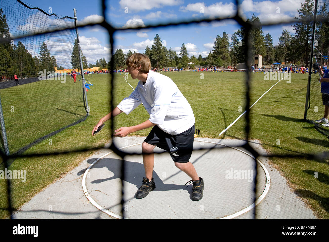 A middle school boys discus throw during a school track and field meet on the field of a local junior high school, - Stock Image
