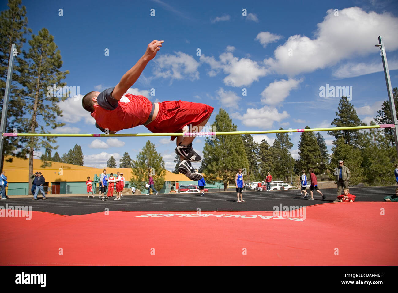 A middle school boys high jump during a school track and field meet on the field of a local junior high school - Stock Image