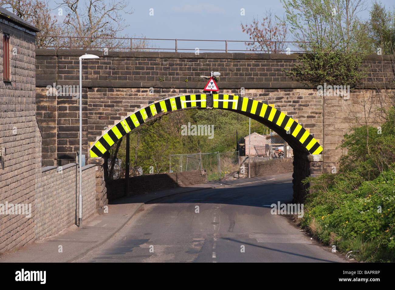 Low roadbridge with yellow and black striped warning markings - Stock Image