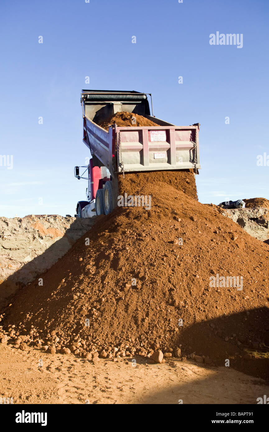Dump Truck Dumping Fill Dirt Into Excavated Basement For