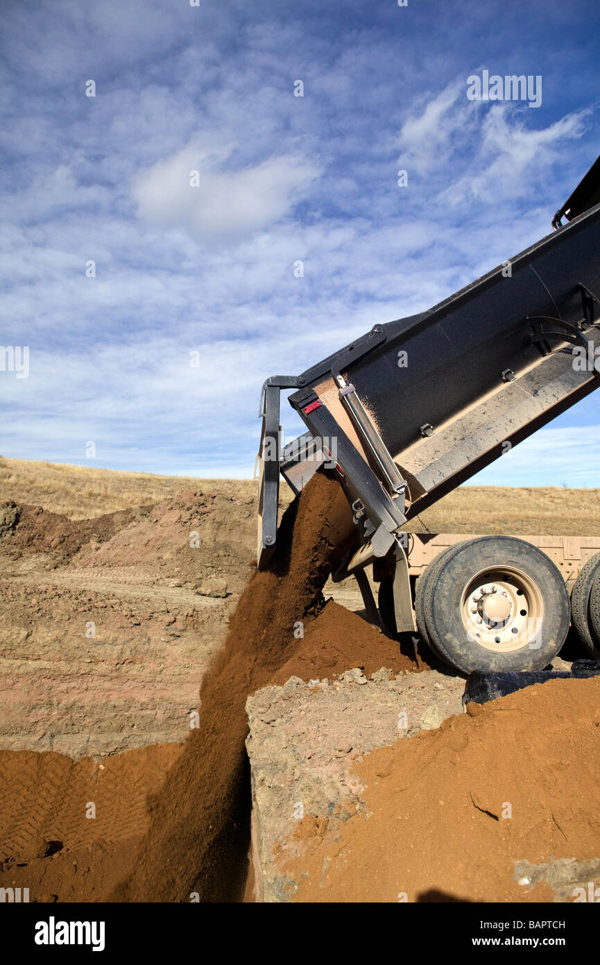 Dump truck dumping fill dirt into excavated basement for new residential houses - Stock Image