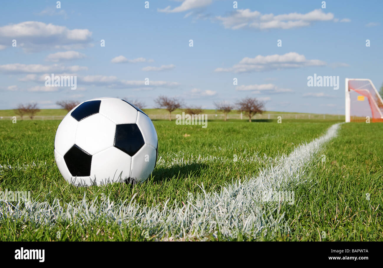 Soccer ball in corner pitch area against blue sky - Stock Image